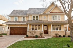 Beautiful-beige-country-house-with-brown-wooden-garage-door-design-also-gray-brick-drive-way-and-green-court-decoration